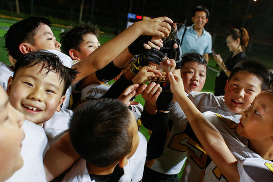 Eagles players celebrate after they defeated the Sharklets in a Future League American football youth league match in Beijing