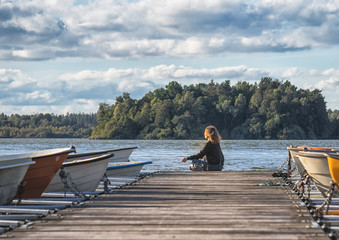 Woman is sitting on the wooden pier with boats