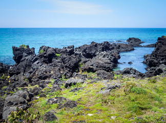 Idyllic sand beach with volcanic black rocks in Jeju Island, South Korea