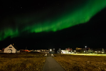 Northern lights and starlight sky over the settlement with living houses and road, Nuuk, Greenland