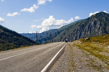 Chuiski road, Altai Republic. The road in the mountains, highway, paved road near the shore of the river Chuya. Sunny day in summer. Biking, cycling, cyclist.