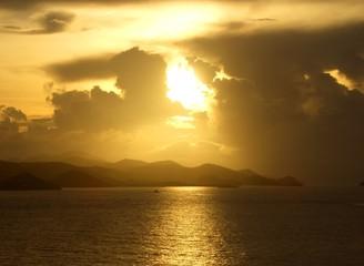 sunrise sunset over sea with distant coastline and sunbeam