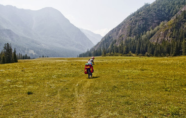 Biking in the Altai region. Russia, the Republic of Altai. Biking in Beluha area. A young woman, girl riding a bicycle. Sports hiking. Around the mountain, green, blue sky. Tourism.