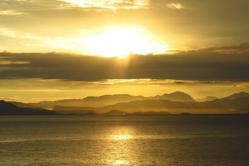 sunrise sunset over sea with distant coastline