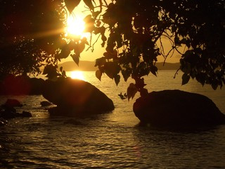 sunset sunrise behind boulders in the sea