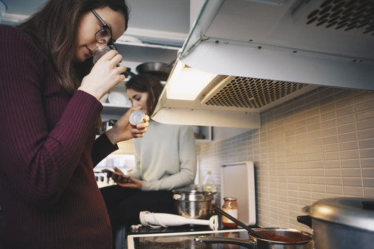 Woman smelling ingredient in bottle while cooking food