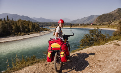 Russia, the Republic of Altai. Biking in Beluha area. Young woman girl standing with a bicycle. Portrait. Sports hiking. Around the mountains, greenery, blue sky, river Katun.