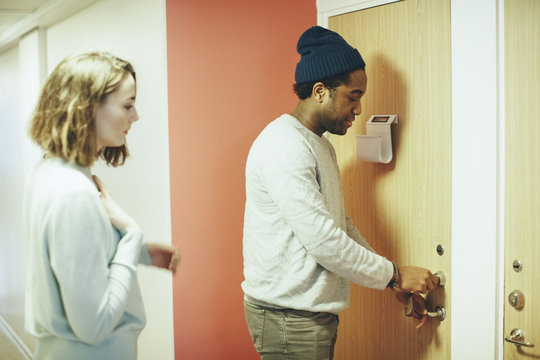 Woman looking at male friend opening door lock in college dorm