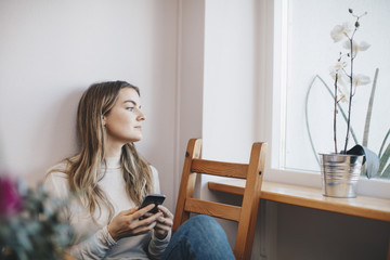 Young woman sitting with mobile phone on chair while looking through window at dorm