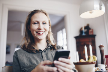 Low angle portrait of young woman using mobile phone at home