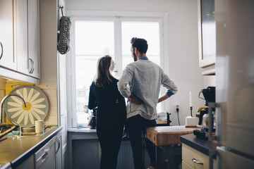 Rear view of couple talking while standing by dining table against window at home