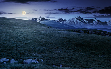 meadow with huge stones on top of mountain range at night