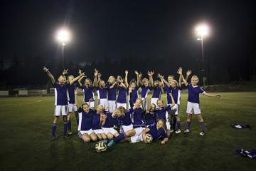Portrait of cheerful girl's soccer team on illuminated field against sky