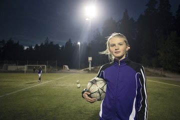 Portrait of girl standing with soccer ball on field against trees at night