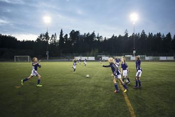 Girls running during soccer drills on field