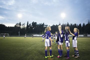 Girls standing on soccer field against sky