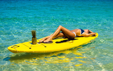 Young tanned woman lies on a yellow SUP surfboard. She swims on the waves in the ocean serenely. Relax to get away from problems. Concept