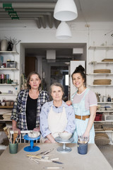 Portrait of female potters by workbench at ceramics store