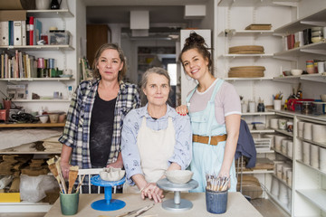 Portrait of smiling female potters by workbench at ceramics store