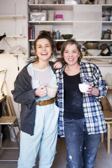 Portrait of happy female potters standing with arm around at workshop
