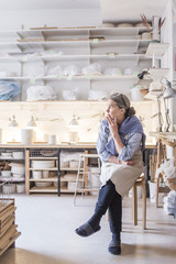 Senior female potter looking away while sitting on stool against shelves in workshop