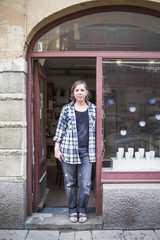 Portrait of mature female ceramic store owner standing at doorway