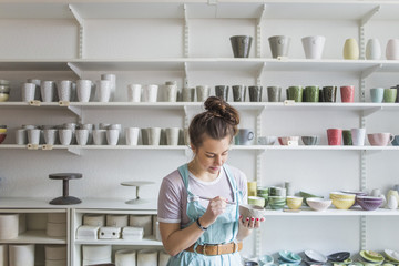 Young female potter using hand tool on vase while standing against shelves at store