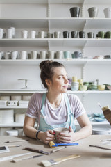 Young female potter sitting at workbench while looking away against shelves at store