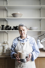 Senior female potter standing with pitcher against shelves at workshop