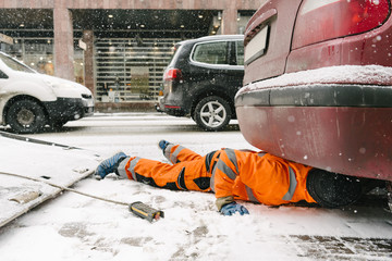 Tow truck driver lying on road by car in city during winter