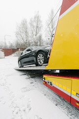 Black car on tow truck during winter