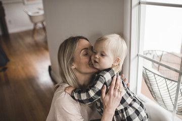 Happy mother kissing daughter by window at home