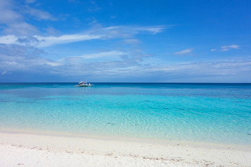 White clouds and Banca boat on blue sky over calm sea. Clear blue water with fantastic white sand beach. Summer outdoor nature holiday serenity. Kalanggaman Island, Philippines. Background,