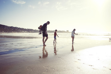 Full length of father with children walking at beach on sunny day
