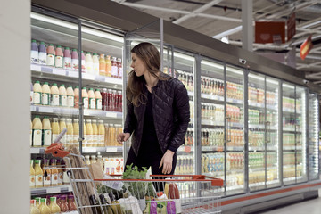Woman standing with shopping cart while looking at bottles in refrigerated cabinet
