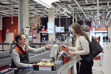 Mature cashier talking to woman while paying at checkout counter in supermarket