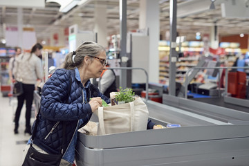 Mature woman putting groceries at checkout counter in supermarket