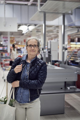 Smiling mature woman carrying shopping bag while looking away against checkout at supermarket