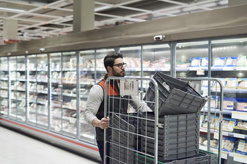 Sales clerk pushing cart with plastic crates at supermarket