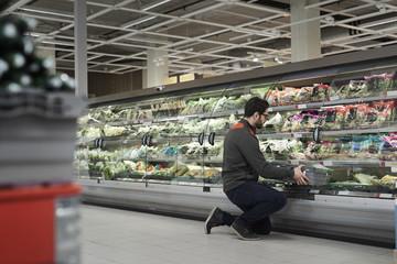 Side view of sales clerk kneeling while arranging crate in cabinet at supermarket