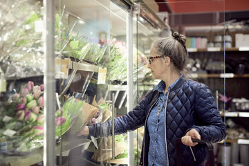 Mature woman buying flowers from glass cabinet at supermarket