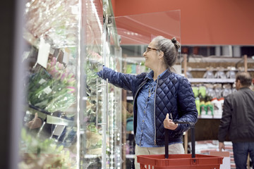 Smiling woman buying flowers while holding shopping basket at supermarket