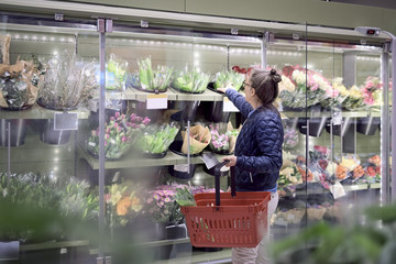 Side view of woman buying flowers from glass cabinet at supermarket