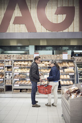 Mature couple standing with basket against bread rack at supermarket
