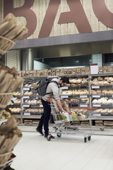 Man keeping paper bag in shopping cart while standing by bread rack at supermarket
