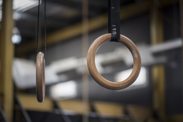 A pair of gymnastic  rings hanging in a gym with an out of focused or blurred background