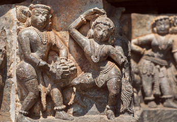 Ruined dancing people on relief of the 12th century Hoysaleshwara temple in Halebidu, India.