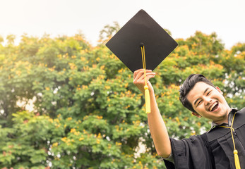 student graduate holding certificated in hand with in the garden