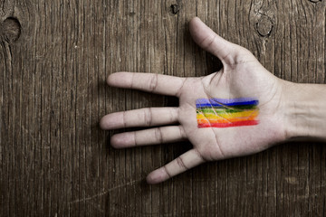 man with a rainbow flag painted in his hand