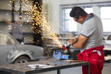 Mechanic using angle grinder in car workshop Fotoväggar